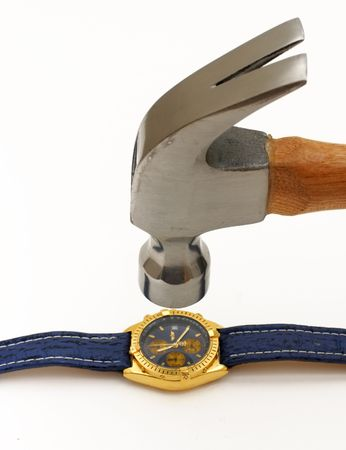 A wooden based iron hammer on its way to smash a classy and expensive wristwatch