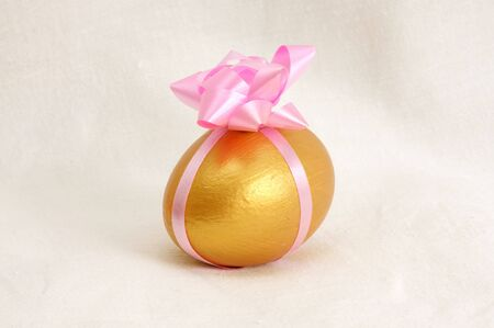 A golden egg wrapped in a pink ribbon with a white fabric as background