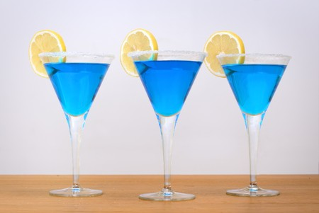 3 Blue cocktails with sugar covered rims and a juicy lemon.
