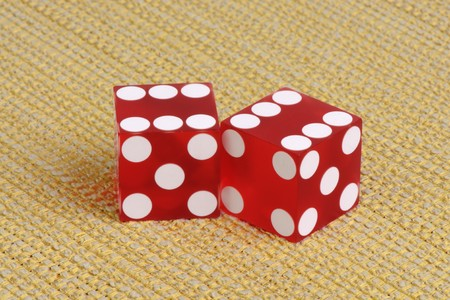 Authentic casino dice on a golden striped fabric. Stock Photo