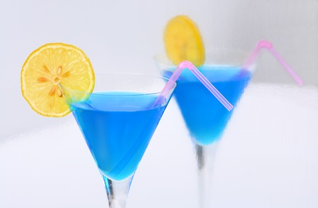 A blue cocktail with a lemon & a straw reflected in a silvery surface.