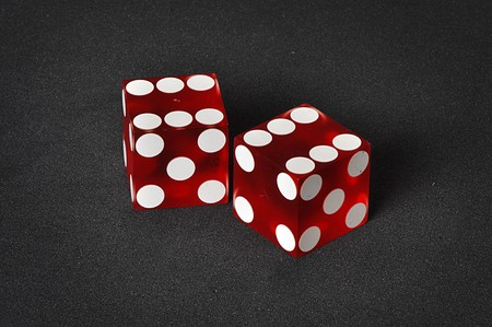 Red and white casino dice on a unique black background