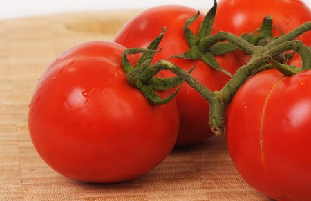 a close-up of fresh tomatos and their leaves Stock Photo