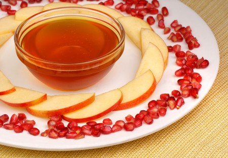 jewish new year: A bowl of honey, apple slices and pomegranate  seeds on a plate with a golden fabric underneath
