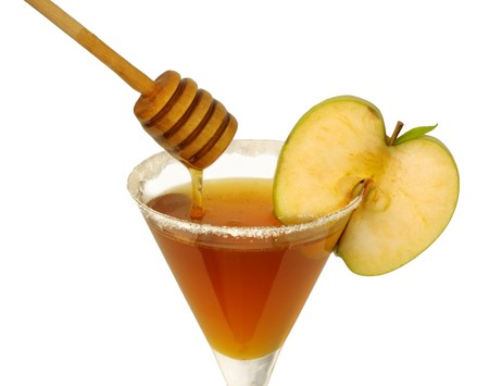 Honey in a cocktail glass with apple and sugar on the rim and a wooden drizzler pouring honey. (Apple and honey is a tradional food on the Jewish new year)