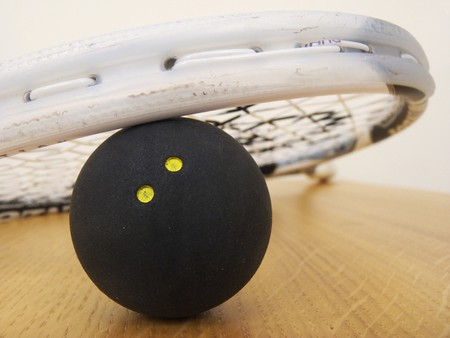 A Squash racket leaning on a Squash ball