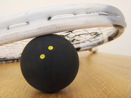 A Squash racket leaning on a Squash ball