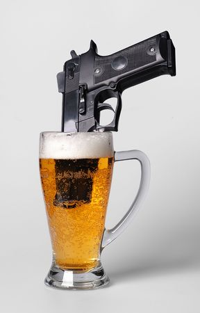 A pistol in a beer glass Stock Photo