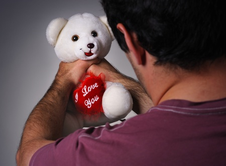 Frustrated man strangling a valentine teddy bear Stock Photo