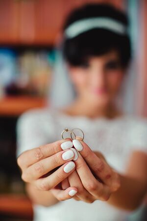 platinum hair: Happy bride is holding two wedding rings in her hands Stock Photo