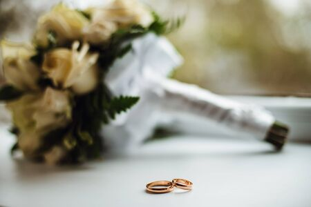 solemnization: Two golden wedding rings with a bouquet on background