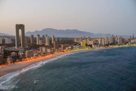 Breathtaking view of the coastline in Benidorm at sunset with high buildings, mountains, sea and city lights
