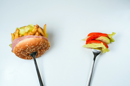 impasse: Healthy or junk food choice. Two forks: one with burger and another with fresh vegetables
