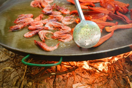 conceptional: Prosess of cooking traditional spanish dish paella on fire. Prawns and red pepper Stock Photo