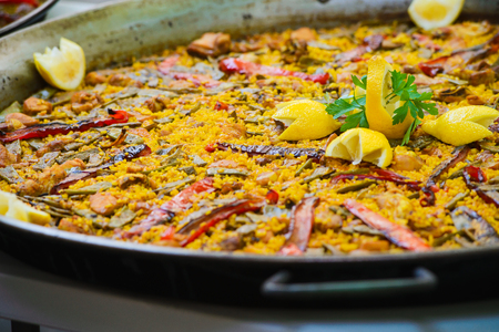 conceptional: Closeup of a traditional tasty spanish dish paella served with meat, lemon and vegetables