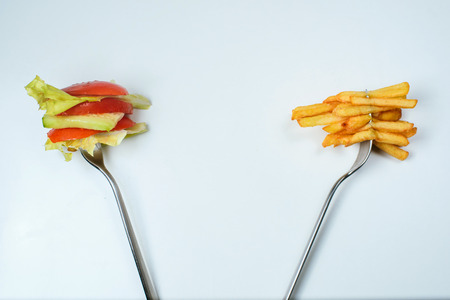 impasse: Healthy or junk food choice. Two forks: one with french fries and another with fresh vegetables Stock Photo