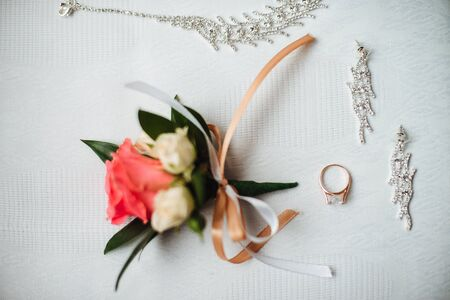 buttonhole: Closeup of buttonhole, golden wedding ring and brides jewelry