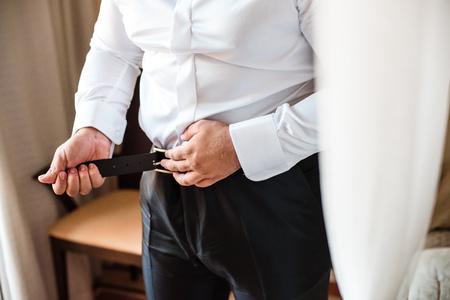 Groom holding hands on the belt, wedding suit Zdjęcie Seryjne