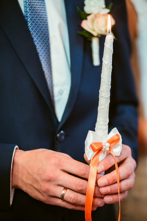 christian marriage: Closeup of a groom in suit holding burning candle in church Stock Photo