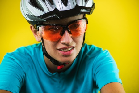 Close-up portrait of a wet tired female cyclist wearing helmet and sport glasses