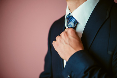 suit  cuff: Groom is holding hands on the tie, wedding suit
