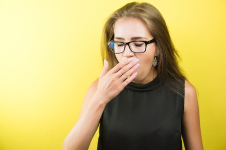 Portrait of a young tired yawning female business lady wearing spectacles