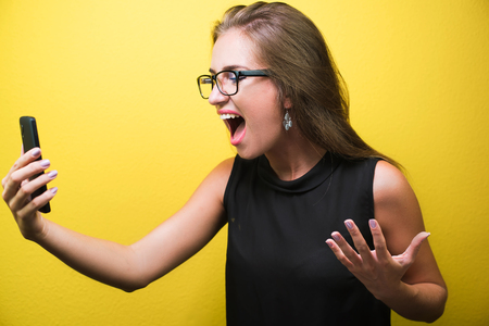 Portrait of a young angry and stressed business woman shouting at a mobile phone