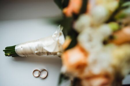 Two golden wedding rings with a bouquet on background
