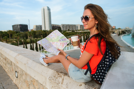 Happy female tourist with a map and backpack at a wonderful City of Arts and Sciences in Valencia, Spain