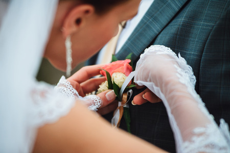 buttonhole: Closeup of a bride wearing a buttonhole on a groom Stock Photo