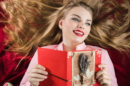 atmosphere: Young smiling happy blonde girl with long hair lying on red background and holding hand made card with lavender in her hands. Valentines Day, Christmas, Birthday gifts. Stock Photo