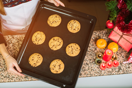 Close-up of woman wearing apron showing baked chocolate cookies at kitchen close to the the Christmas tree, gifts, candles and mandarins. Christmas and New Year holidays Stock Photo