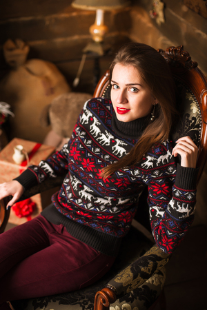 Young cute happy girl in sweater with deer print smiling and sitting in chair close to Christmas tree and gifts on wooden background. New Year and Christmas celebration 版權商用圖片