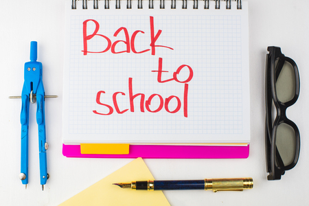 School supplies on a table with written words back to school in a notebook Stock Photo