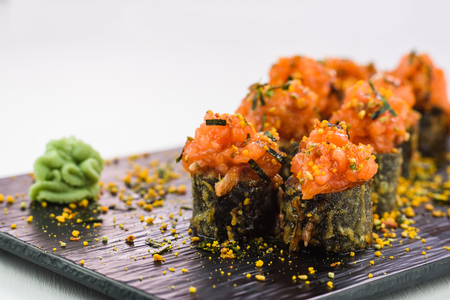 Hot and Fried Sushi and Rolls with Seafood, Vegetables, Cream Cheese served with wasabi on a black stone plate isolated on a white background Stock Photo