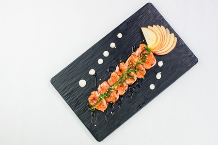 Top view of Japanese tasty tataki dish of salmon served with apple and kelp. Isolated on white background Stock Photo
