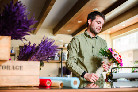 Male attractive smiling florist wearing green shirt and making bouquet in a flower shop. Man assistant or owner in floral design studio, making decorations. Flowers delivery, creating order Foto de archivo