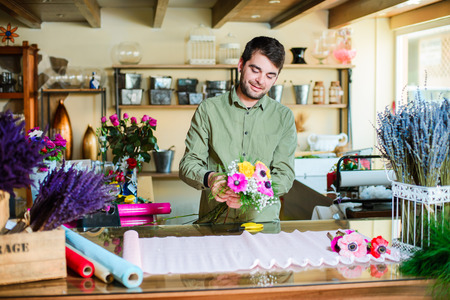 Male attractive smiling florist wearing green shirt and making bouquet in a flower shop. Man assistant or owner in floral design studio, making decorations. Flowers delivery, creating order Stock Photo