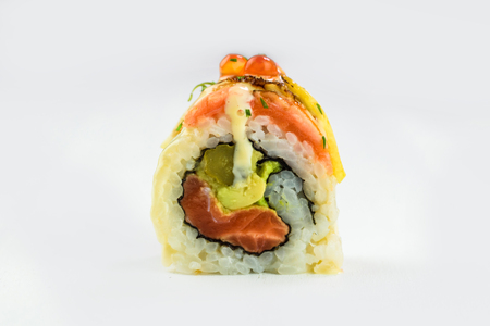 Japanese traditional sushi roll with salmon, avocado and caviar isolated on a white background. Closeup
