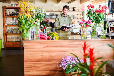 Male attractive florist taking notes in a notebook in a flower shop. Man assistant or owner in floral design studio, making decorations. Flowers delivery, creating order