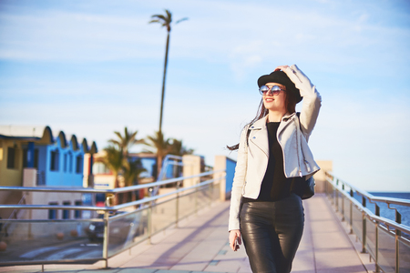 Happy young attractive girl blogger wearing black hat and round sunglasses is walking by the sea with a cell phone in hand. Denia, Spain. Stock Photo