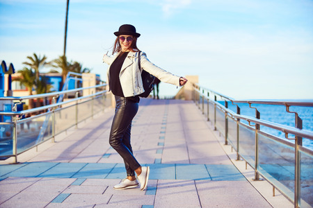 Happy young attractive girl blogger wearing black hat and round sunglasses is rejoicing while walking by the sea on a sunny day. Denia, Spain. 스톡 콘텐츠
