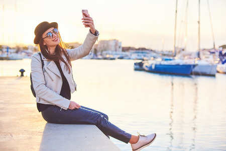 Happy young long-haired woman blogger wearing black hat and round sunglasses is smiling while making a selfie with a cell phone at the sunset in a port with sea and boats on background. 스톡 콘텐츠