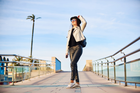 Happy young attractive girl blogger wearing black hat and round sunglasses is walking by the sea with a cell phone in hand. Denia, Spain. 스톡 콘텐츠