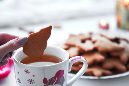Close-up of woman hand dunking homemade gingerbread cookie into tea. Cozy atmosphere. New Year and Christmas holidays. Stock Photo