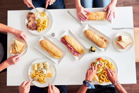 Overhead view of friends having dinner at a restaurant table. Grilled steaks, French fries, salad, sandwiches and fried squid on white table.