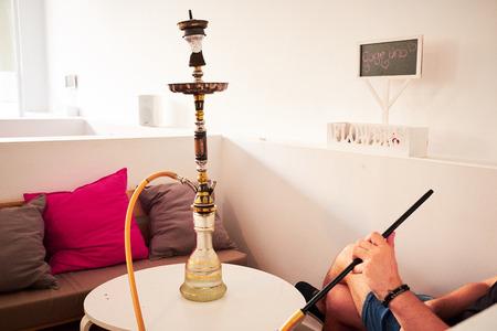 Male hand holding hookah pipe while smoking shisha at lounge bar.