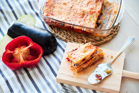 Very tasty homemade vegetarian lasagna with eggplant and tomatoes, sauce bechamel on the wooden table. Foto de archivo