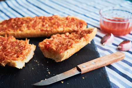 Close-up of tasty toasts made of baguette, tomatoes and melted cheese. Typical Spanish breakfast.