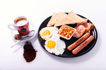 Close-up of traditional full English breakfast with fried eggs, sausages, beans, bacon, toasts and orange juice isolated on white background.